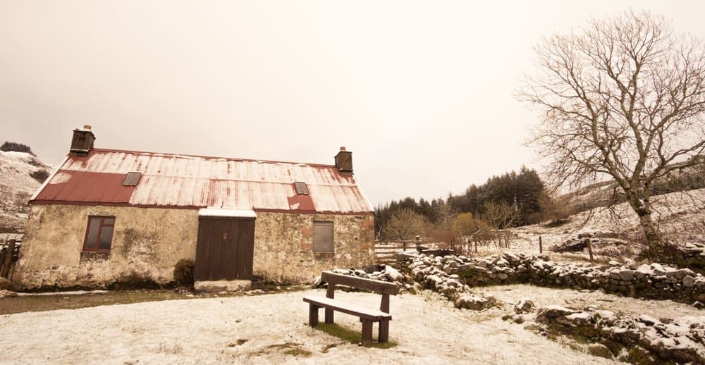 Image shows snow covered ground, a bench seat and a snow covered red roofed stone cottage (painted white a long time ago)